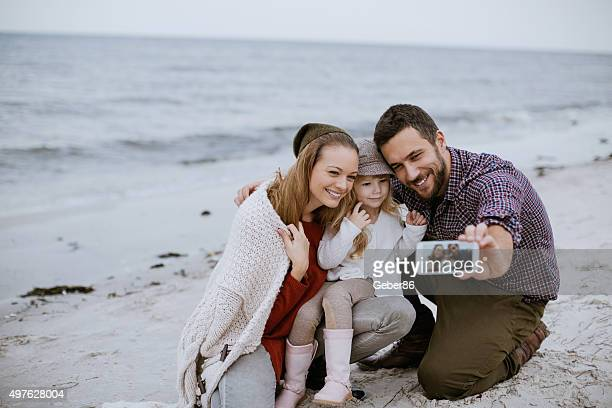 Family taking photos at the beach