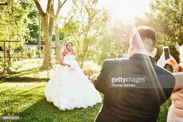 family taking photos with smartphones of young woman in quinceanera gown in backyard - 14 15 anni foto e immagini stock