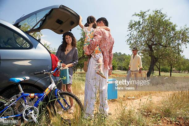 family taking picnic things out of a car