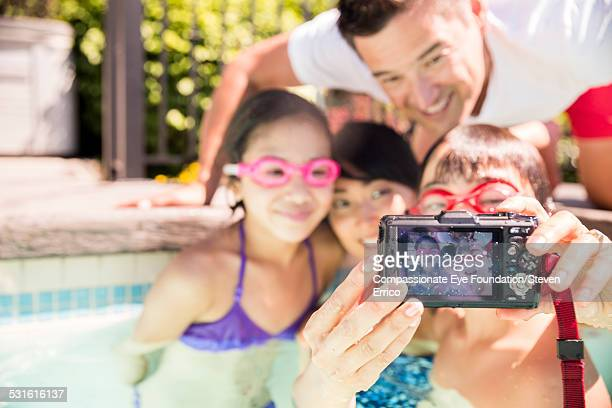 Family taking picture of themselves in pool