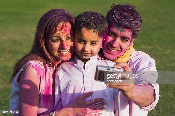 Family taking picture of themselves with a digital camera on Holi