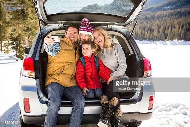 Family taking self portrait on tailgate