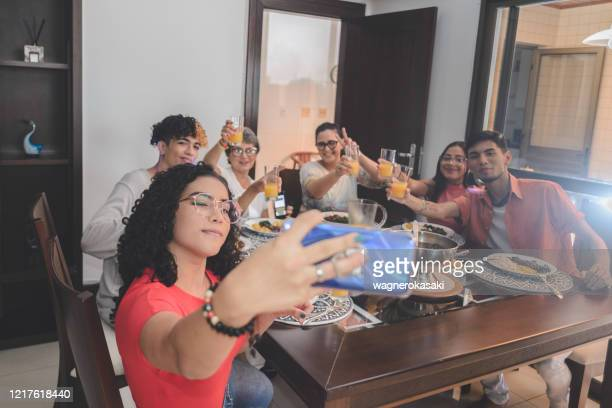 family taking selfie around the dining table served with feijoada, typical brazilian black bean stew - feijoada imagens e fotografias de stock