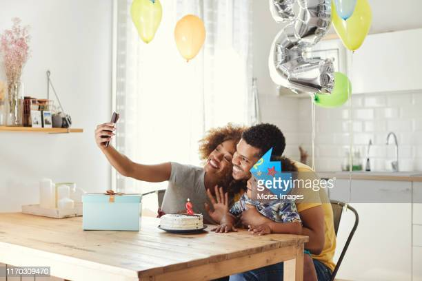 family taking selfie during birthday celebration - happybirthdaycrown stock pictures, royalty-free photos & images