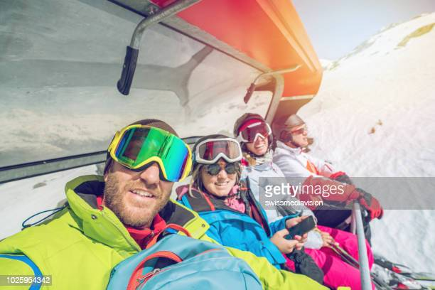 family taking selfie from ski lift in switzerland, ski holidays 4 people enjoying swiss alps and vacations concept - ski lift stock pictures, royalty-free photos & images