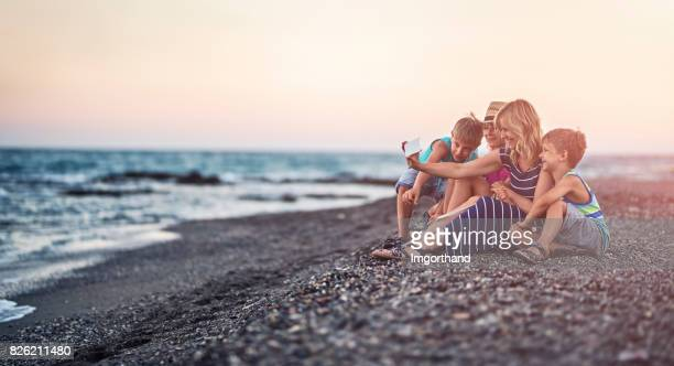 Family taking selfie on a beach in the evening