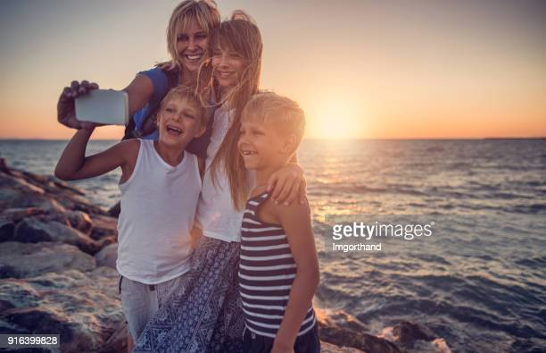 family taking selfie on a beach in the evening - finale foto e immagini stock