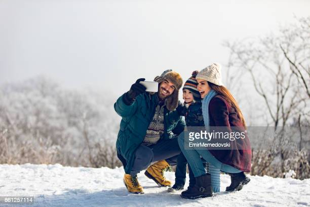 Family taking Selfie on winter day in the forest.