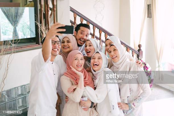 family taking selfie together celebrating hari raya aidilfitri (eid al-fitr) - eid mubarak stock pictures, royalty-free photos & images