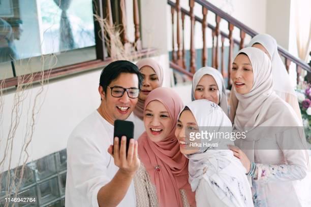 family taking selfie together celebrating hari raya aidilfitri (eid al-fitr) - eid ul fitr photos stock pictures, royalty-free photos & images