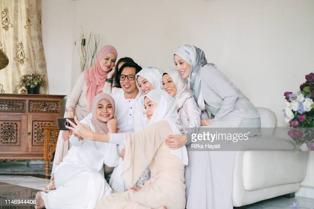 family taking selfie together celebrating hari raya aidilfitri (eid al-fitr) - hari raya celebration stock pictures, royalty-free photos & images