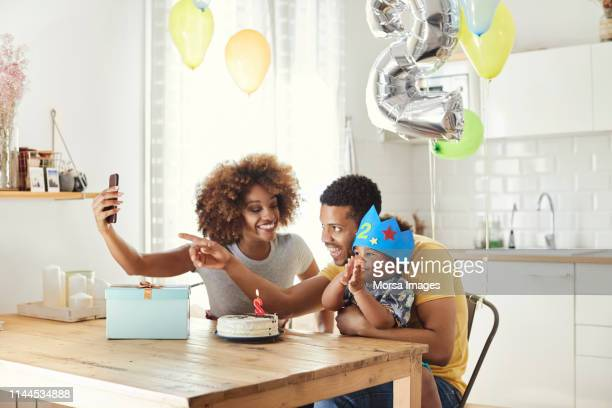 family taking selfie while celebrating birthday - happybirthdaycrown stock pictures, royalty-free photos & images