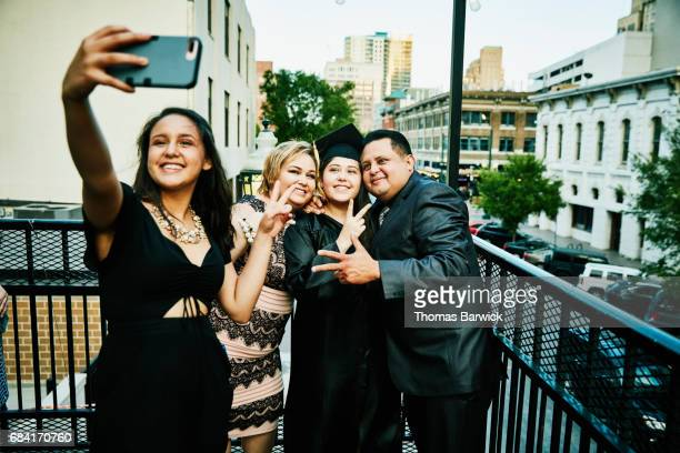 Family taking selfie with smartphone while celebrating daughters graduation on restaurant deck