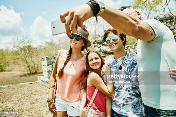 Family taking selfie with smartphone while exploring ruins during vacation