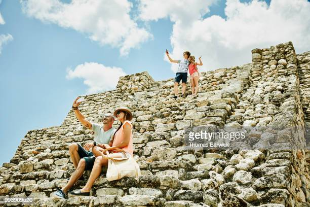 Family taking selfies with smartphones while exploring Mayan ruins during vacation