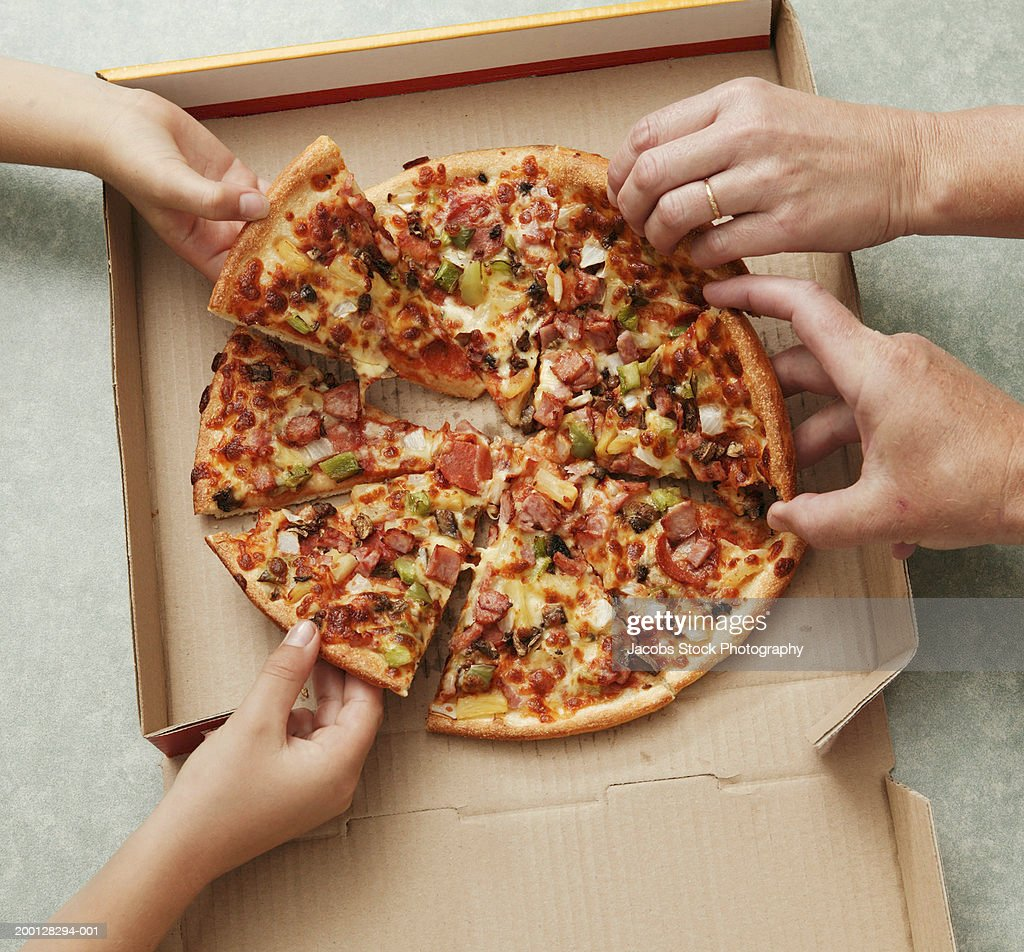 Family taking slices of pizza from pizza box, elevated view : Stock Photo