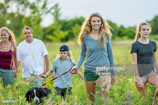 family taking their dog on a walk - fat hairy men stock photos and pictures