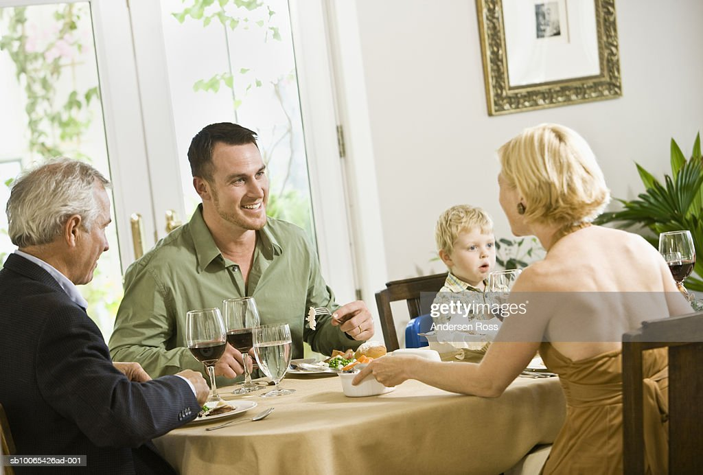 Family talking at dinner table with son (2-3 years) looking on : Foto stock