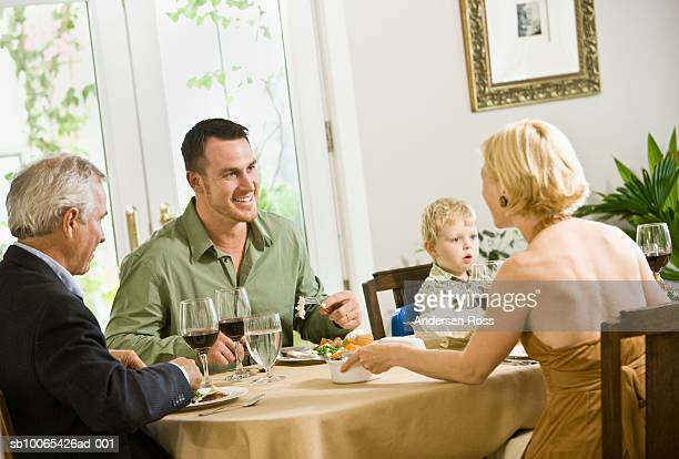 family talking at dinner table with son (2-3 years) looking on - 55 59 years stock pictures, royalty-free photos & images