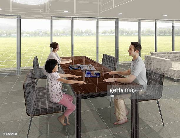 Family talking over table, smiling