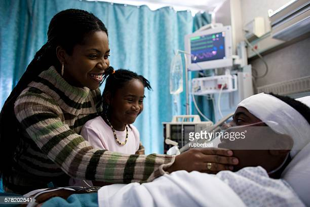 family talking to boy in hospital bed - patients brothers stock pictures, royalty-free photos & images