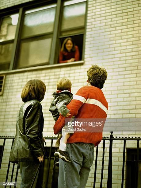 Family talking to woman in window