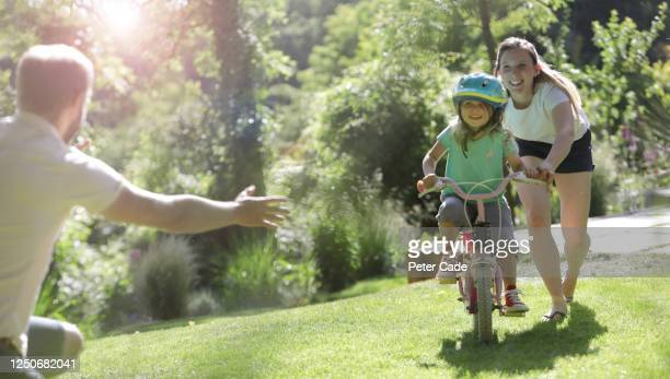 family teaching daughter to ride a bike - extra long stock pictures, royalty-free photos & images