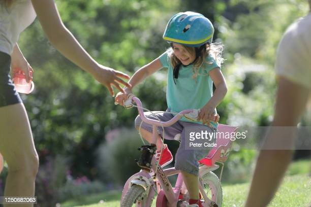 family teaching daughter to ride a bike - first occurrence stock pictures, royalty-free photos & images