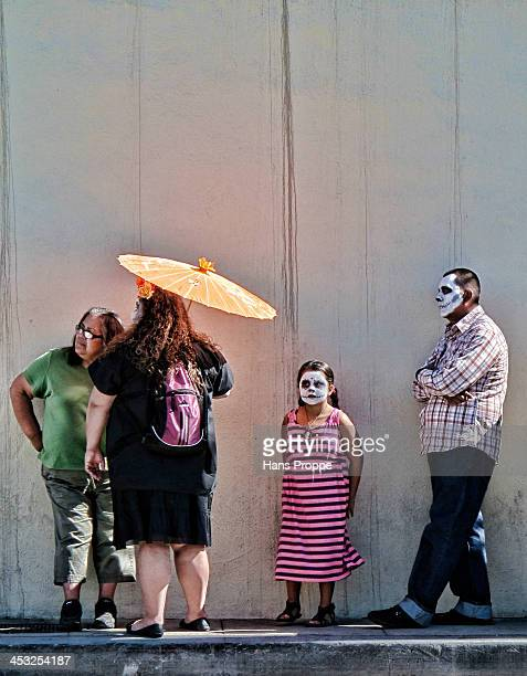 Family that has attended the Day of the Dead gathering at the Hollywood Forever Cemetery is waiting for a bus.