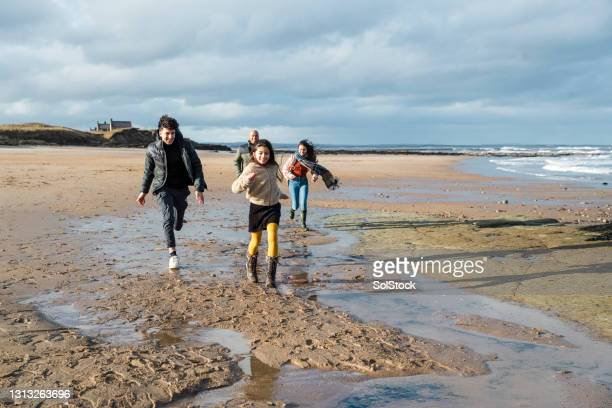 family time at the beach - moving after stock pictures, royalty-free photos & images