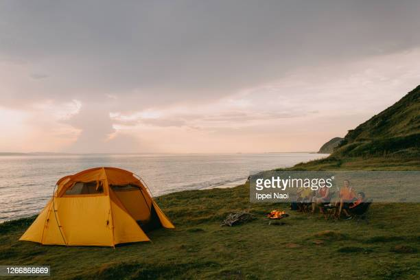family toasting and smiling at camera at campsite by the sea - tent stock pictures, royalty-free photos & images
