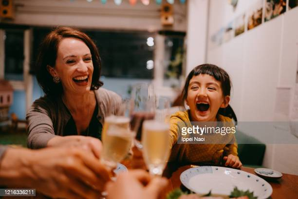 family toasting at dinner table - evening meal ストックフォトと画像
