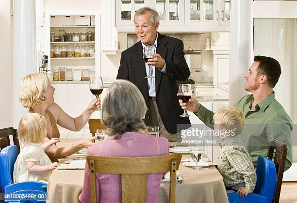 family toasting at dinner table with baby girl (9-12 months) and boy (2-3 years) looking on - 30 39 years stock-fotos und bilder
