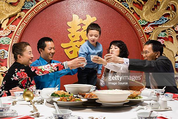 family toasting at reunion dinner - chinese new year stock pictures, royalty-free photos & images