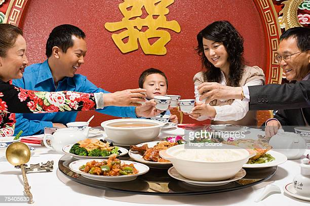 family toasting at reunion dinner - chinese culture stock pictures, royalty-free photos & images