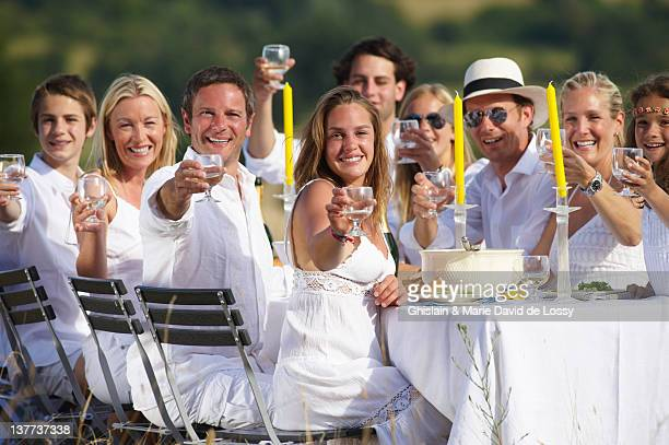 Family toasting at table outdoors
