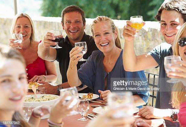 Familie Anstoßen auf Tisch im Freien