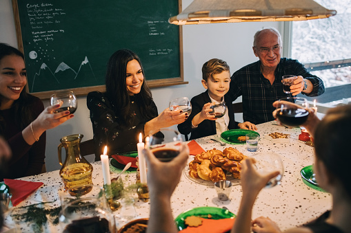 Family toasting drinks while enjoying meal at table during Christmas - gettyimageskorea