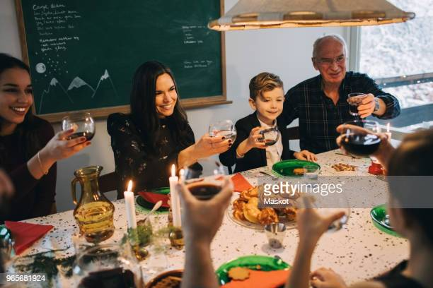 family toasting drinks while enjoying meal at table during christmas - koffie drank stockfoto's en -beelden