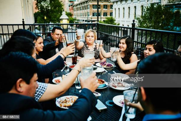 Family toasting during celebration meal on restaurant deck