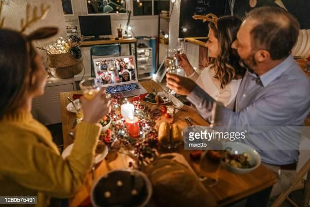 familie toasting auf video-anruf mit nahen und lieben anlässlich der weihnachtsfeier - mother daughter webcam stock-fotos und bilder