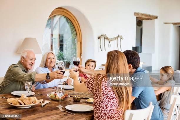 自宅での昼食時にワイングラスを乾杯する家族 - 家族の集まり ストックフォトと画像