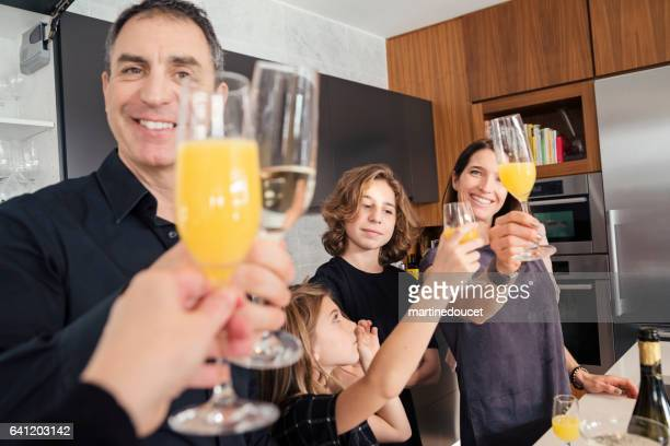 Family toasting with champagne and orange juice at celebration.