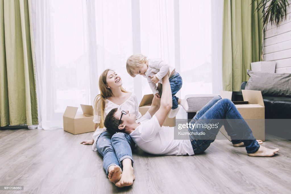 Family together happy young beautiful with a little baby moves with boxes to a new home : Stock Photo