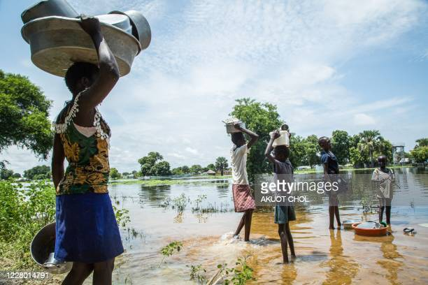 Family try to cross a flooded area after the Nile river overflowed after continuous heavy rain which caused thousands of people to be displaced in...