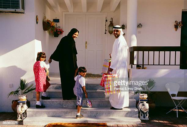 A family turns back and looks at the camera before entering the house.