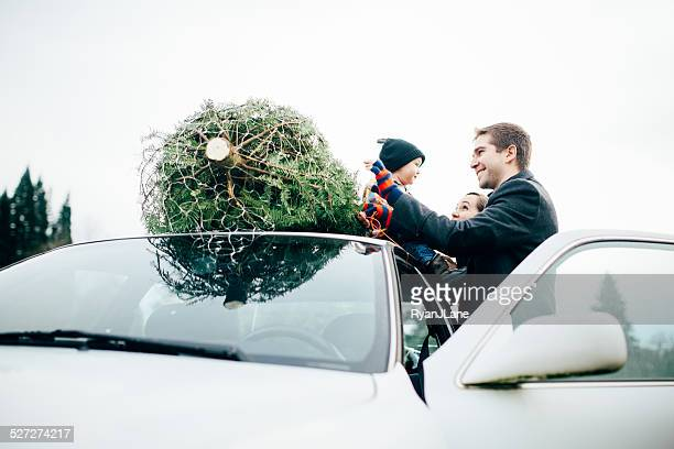 Family Tying Christmas Tree to Car