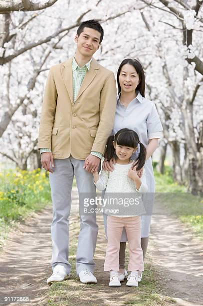 Family under cherry blossom trees, portrait