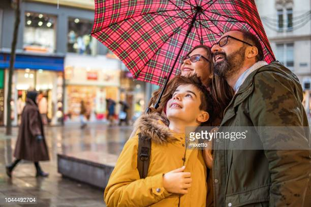 family under umbrella - mother son shower stock photos and pictures