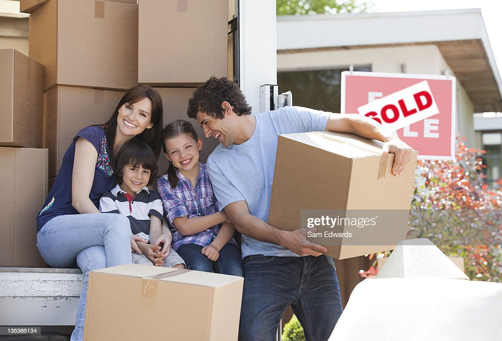 Family unloading boxes from moving van : Stock Photo